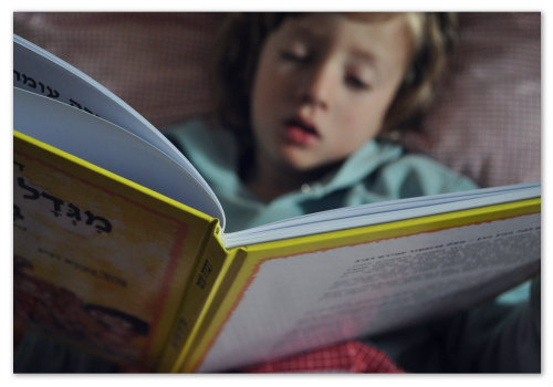 Ребенок читает книгу.