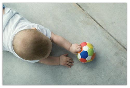 Ребенок играет с мячом.