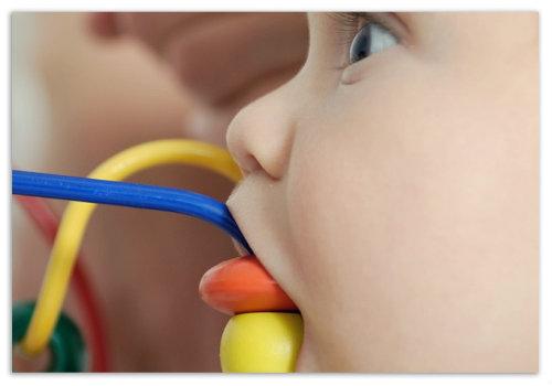 Ребенок облизывает игрушку.
