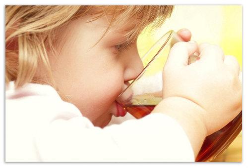 Ребенок пьет чай из кружки.
