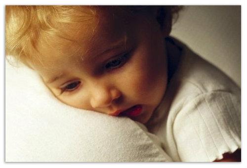 Мальчик грустит на плече у мамы.