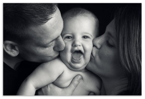 Родители целуют мальчика.
