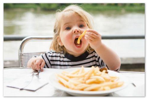 Девочка есть картофель-фри